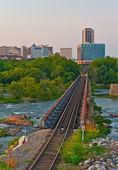 Cityscape of train tracks over a river. — Stock Photo