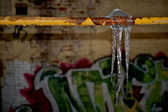Icicles hanging from a pipe — Stock Photo