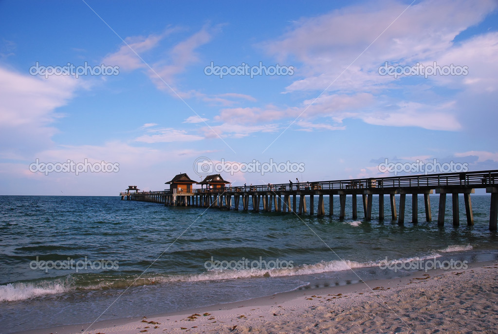 Fishing pier at naples beach florida stock photo for Florida fishing license price
