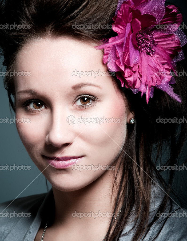 Beautiful young caucasian girl with a pink flower in her hair  Stock Photo #2230778