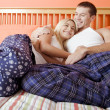 Young Couple in Pajamas Sitting on Bed — Stock Photo #2627572