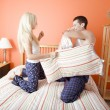 Young Couple Kneeling on Bed Having a Pillow Fig — Stock Photo
