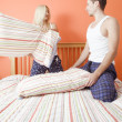 Young Couple Kneeling on Bed Having a Pillow Fig — Stock Photo #2627591