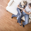 Stock Photo: Young Couple Sitting on Love Seat