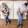 Young Couple Sitting on Love Seat - Stock Photo