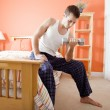 Man Using Arm Weight in Bedroom - Stock Photo