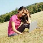 草原にラップトップ上での女の子 — ストック写真