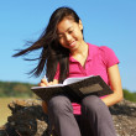 flicka skriver i anteckningsbok — Stockfoto
