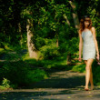 Pretty girl on forest path — 图库照片