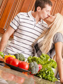 Young Couple Kissing in Kitchen — Stock Photo