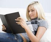 Mladá žena leží na pohovce, čtení knihy — Stock fotografie
