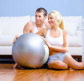 Couple Sitting on Floor With Silver Exercise Bal — Stock Photo