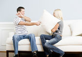 Young Couple Having a Pillow Fight on Sofa — Stock Photo