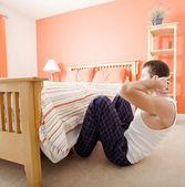 Hombre haciendo abdominales en dormitorio — Foto de Stock