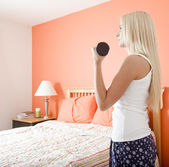 Woman Using Arm Weight in Bedroom — Stock Photo