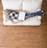 Kadın kanepede kitap ile üstten görünüm — Stok fotoğraf