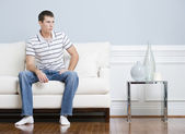Man Sitting on Living Room Couch — ストック写真