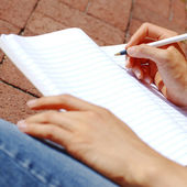 Girl Writing In Note Book — Stockfoto