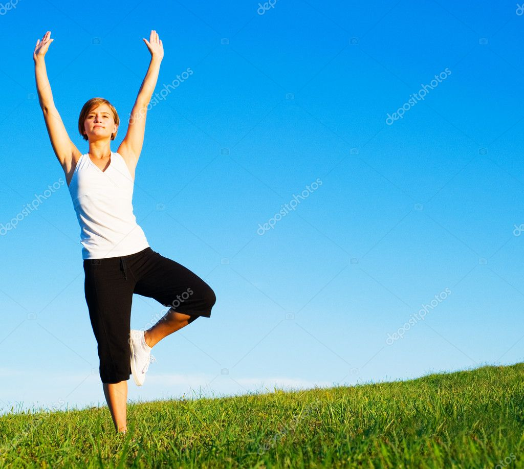 Young woman doing yoga in a sunny meadow, from a complete series of photos. — Foto Stock #2627015