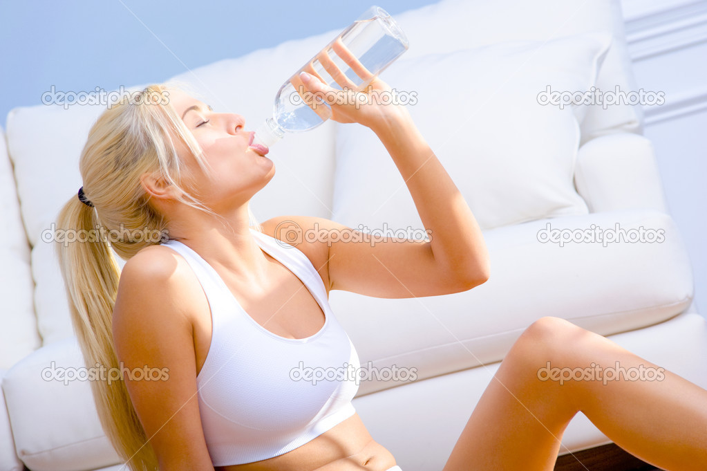 Side view of a young woman in sportswear drinking bottled water  Horizontal shot. — Stock Photo #2627465