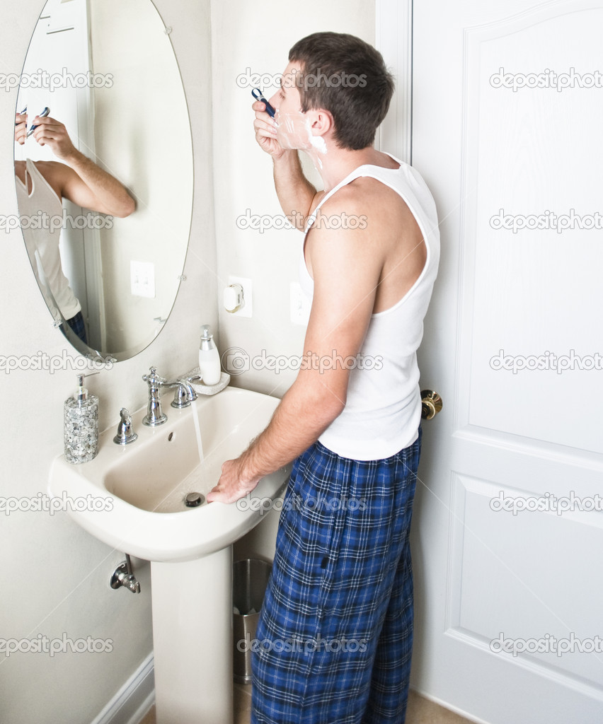 Young man in bathroom shaving stock photo c cardmaverick for Men in bathrooms