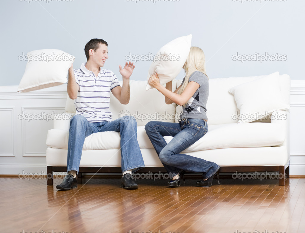 Young couple laugh while having a pillow fight on the sofa. Horizontal shot. — Stock Photo #2627797