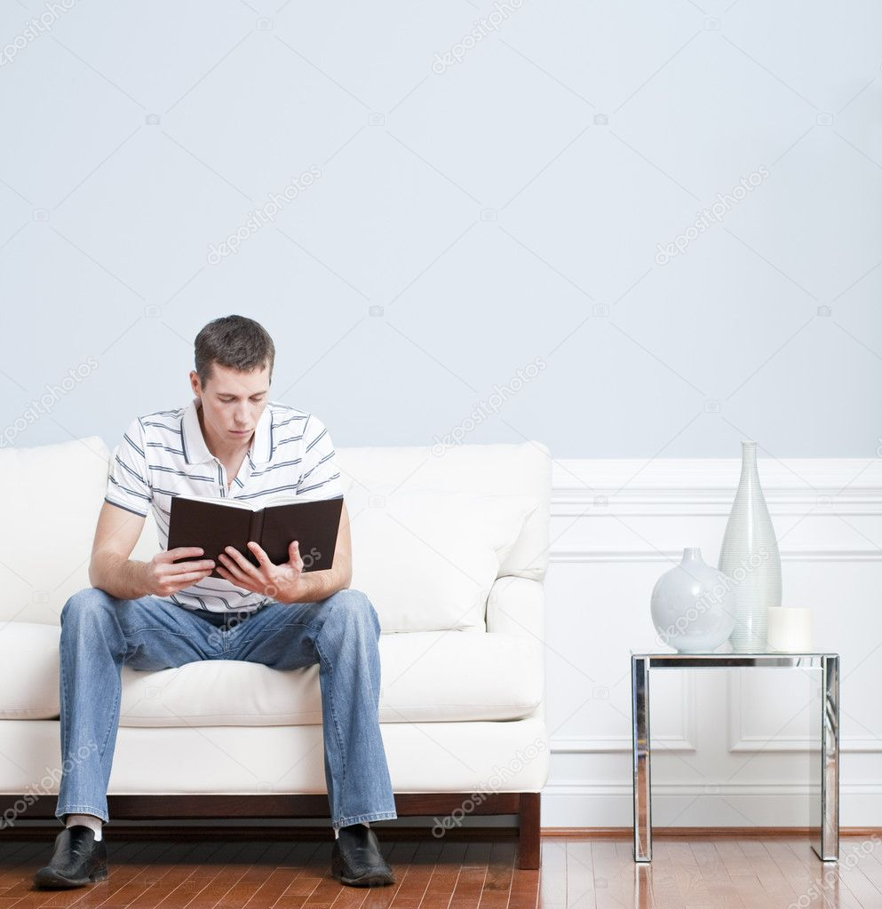 man reading on living room couch stock photo. Black Bedroom Furniture Sets. Home Design Ideas