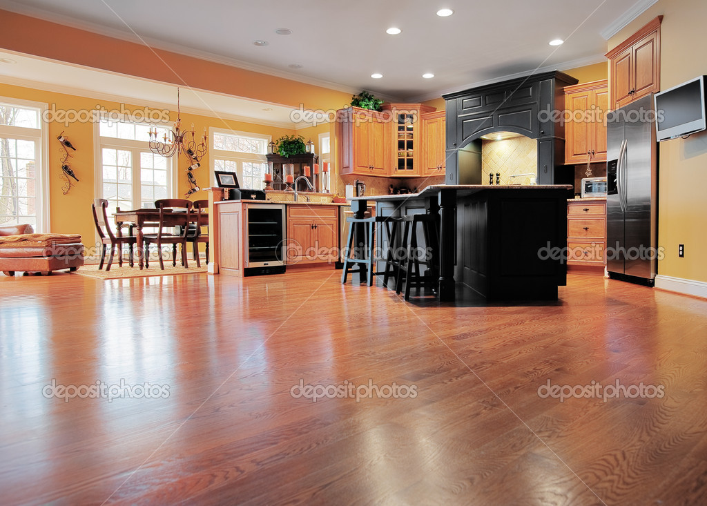 Home interior shows a large expanse of wood flooring in the foreground and a kitchen and dining room in the background. Horizontal format. — Stock Photo #2628139