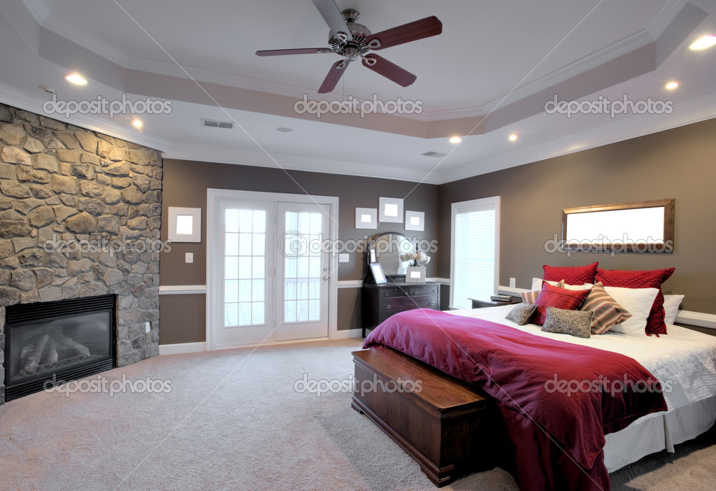 Interior of a large modern bedroom with a fireplace and ceiling fan. Horizontal format. — Stock Photo #2628146