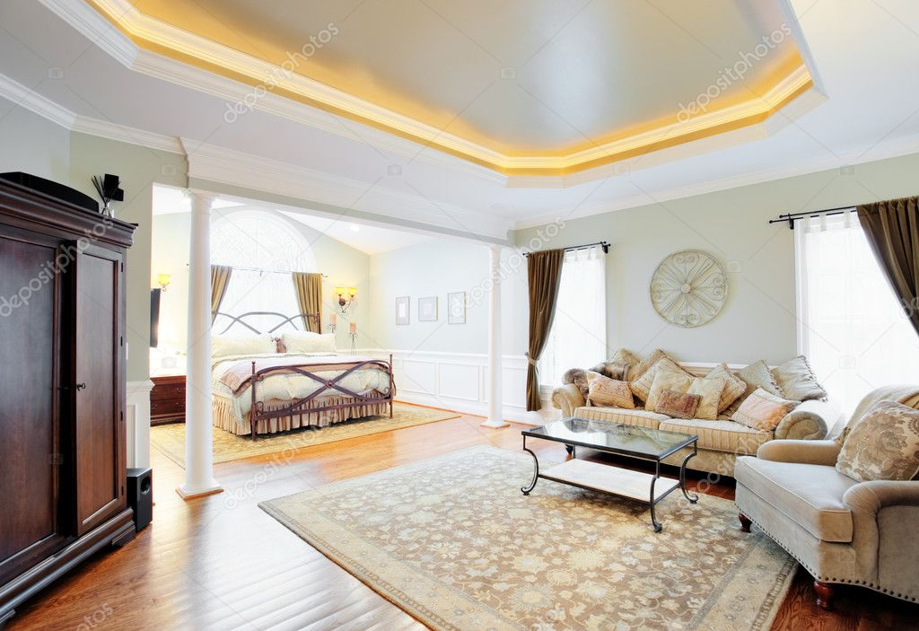 View of a sitting area and bed in a master suite with coved ceiling. Horizontal format. — Stock Photo #2628150