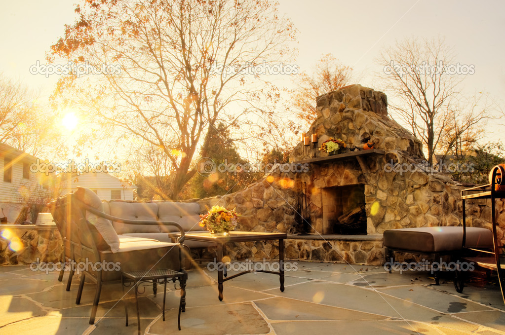 Low angle view of a flagstone patio with an outdoor stone fireplace