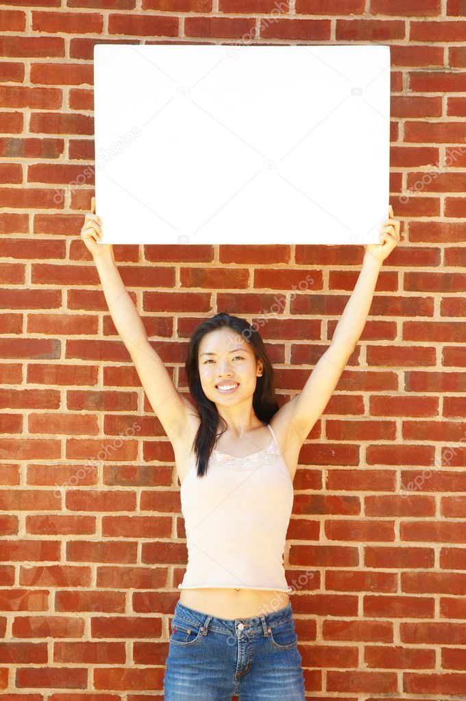 Fashionable girl with blank white poster against brick wall. — Stock Photo #2628640