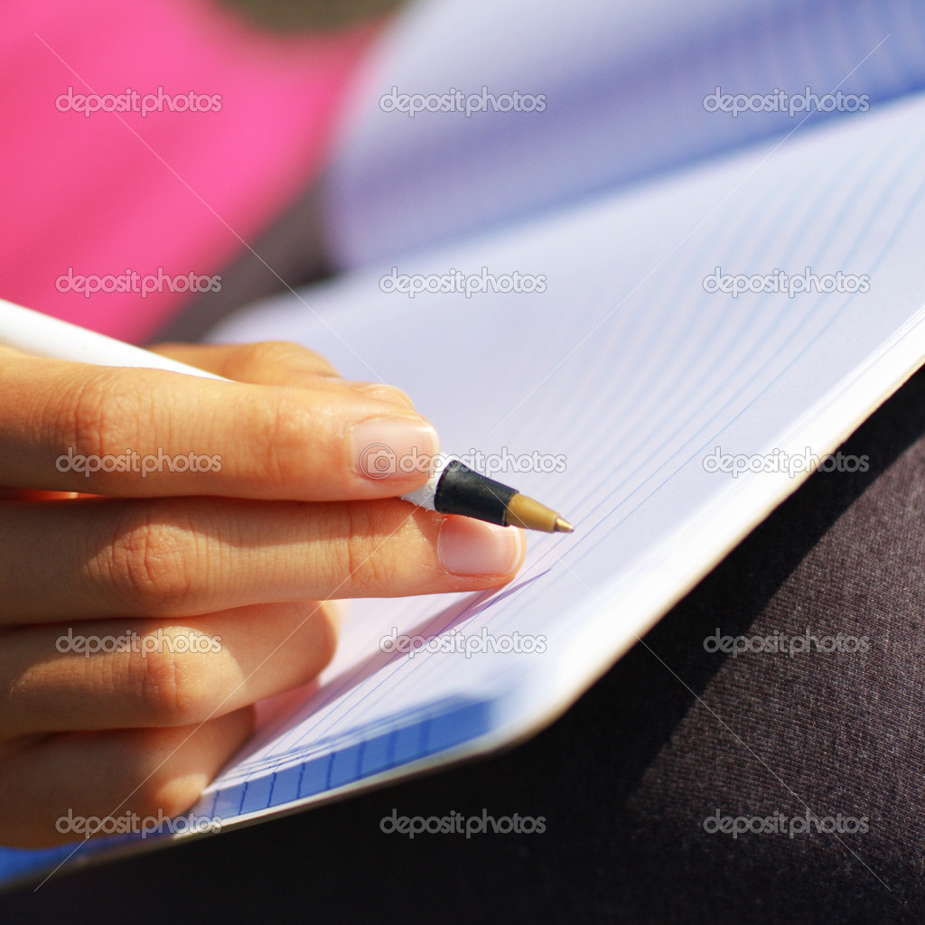 Girl writing in notebook in a field.  Stock Photo #2628752