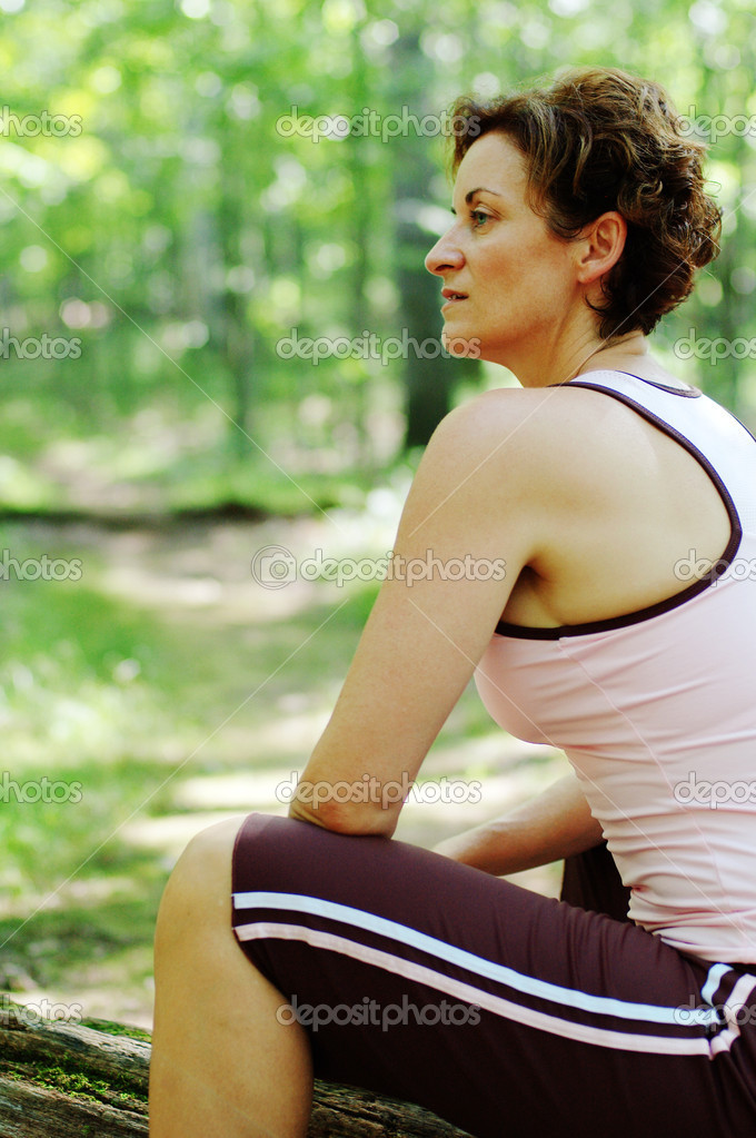 Mature woman runner resting in woods. — Stock Photo #2629413