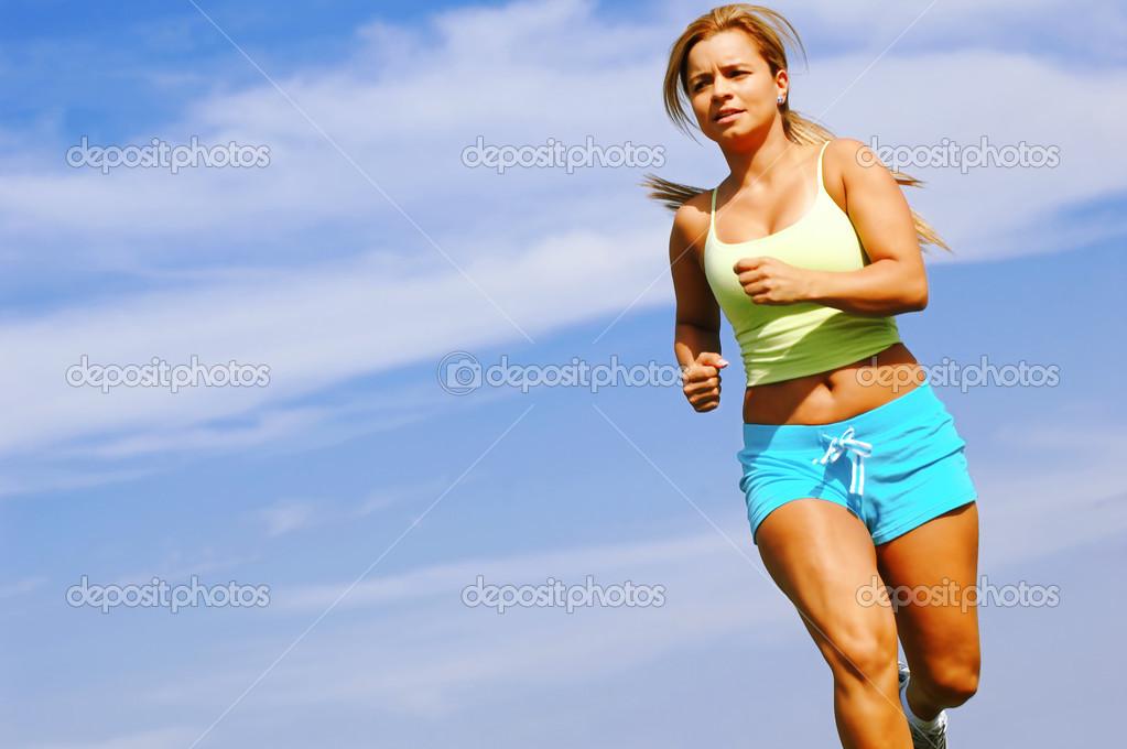Beautiful young woman running against blue sky. — Stock Photo #2629705