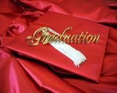 Graduation red cap and gown — Stock Photo