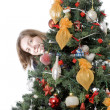 Girl hiding behind christmas tree — ストック写真