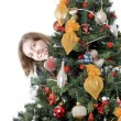 Girl hiding behind christmas tree — Stockfoto