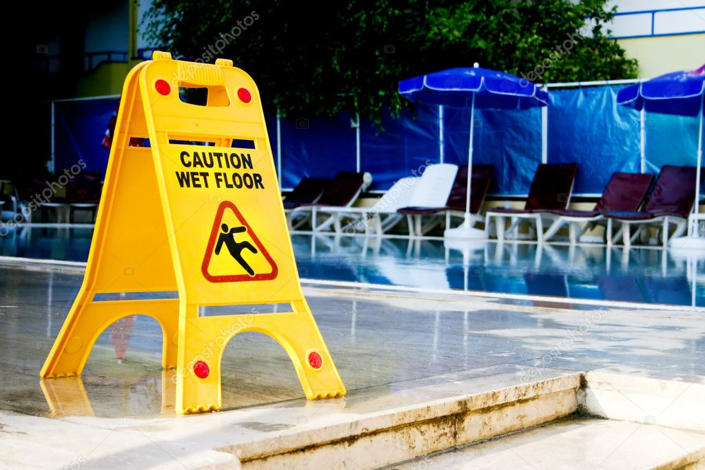 Caution wet floor sign by the pool — Stock Photo #2090114