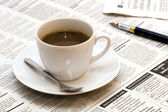 Cup with coffee on newspaper — Stock Photo