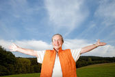 Happy senior woman on a meadow — Stock Photo
