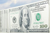 Hundred dollars and blue sky — Stock Photo