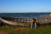 Sad man near the old wooden boat — Stock Photo