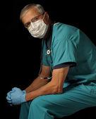 黒の上に座っている中間の高齢者医者 — ストック写真