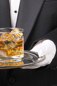 Butler holding whiskey glass on tray — Stock Photo