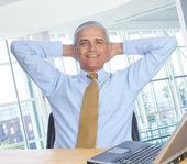 Hombre en manos de escritorio detrás de cabeza — Foto de Stock