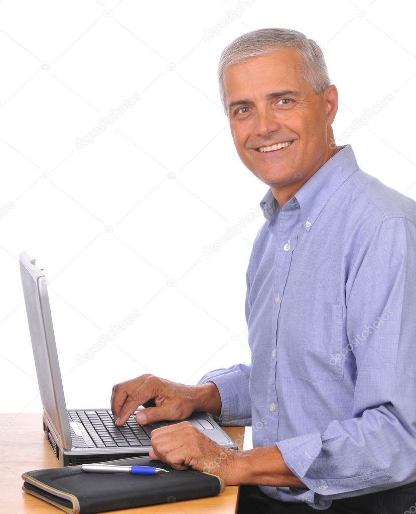 Smiling Mature Businessman Seated at Computer seen from the side isolated on white — Stock Photo #2089613