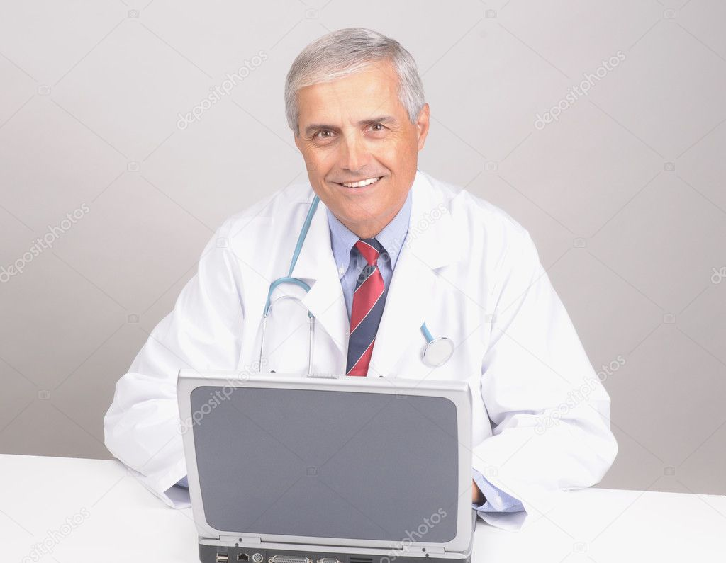 Portrait of a Middle Aged  Male Doctor in Lab Coat with Stethoscope and Laptop Computer over gray background — Stock Photo #2092090
