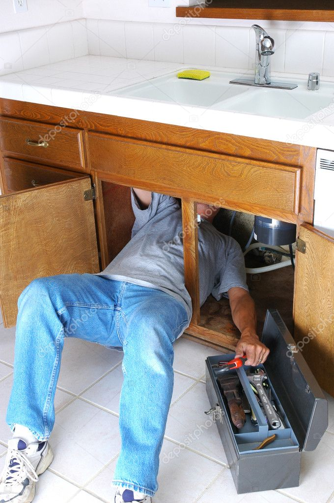 Man with body half under sink cabinet and reaching for wrench in toolbox — Stock Photo #2093741