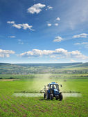 Farming tractor plowing and spraying — Stok fotoğraf